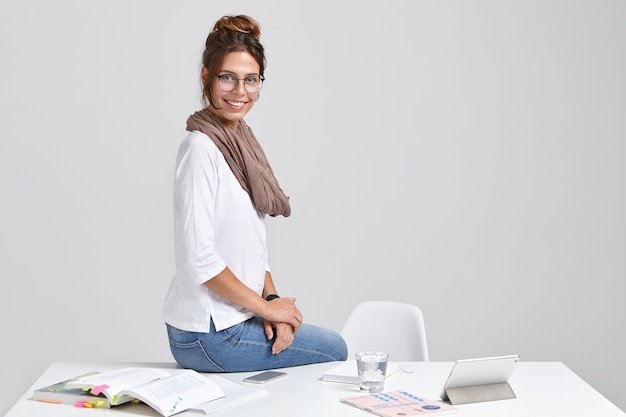 Smiling elegant hipster girl sits at desktop near tablet computer
