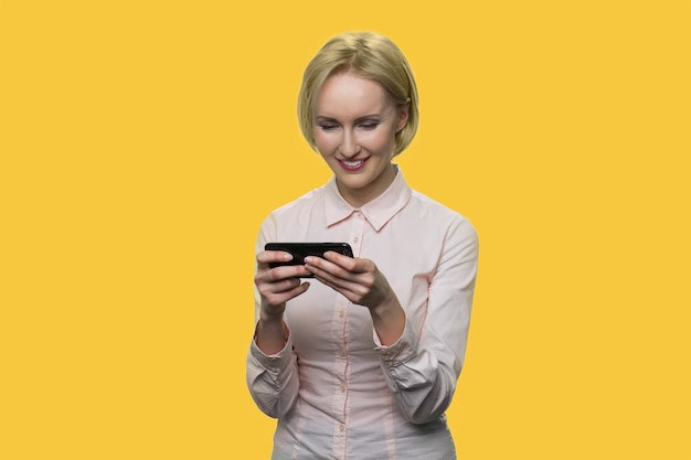 Smiling elegant lady is typing on the smartphone. mature blond caucasinan woman with phone isolated on yellow background.