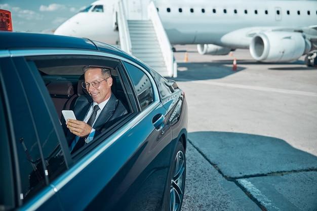 Улыбающийся элегантный мужчина в очках использует мобильный телефон во время трансфера после поездки на самолете