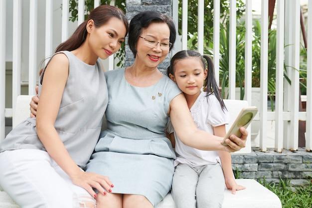 彼女のソーシャルメディアのために大人の娘と孫娘と一緒に自分撮りをしているエレガントな年配の女性の笑顔