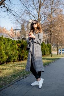 트렌치 코트 산책과 종이 컵에서 커피를 마시는 우아한 여자를 웃 고. 곱슬 머리를 가진 웃는 여자 카메라를 봐 미소 산책 슬로우 모션 얼굴 일몰 아름다운 아가씨 야외 근접 촬영 귀여운