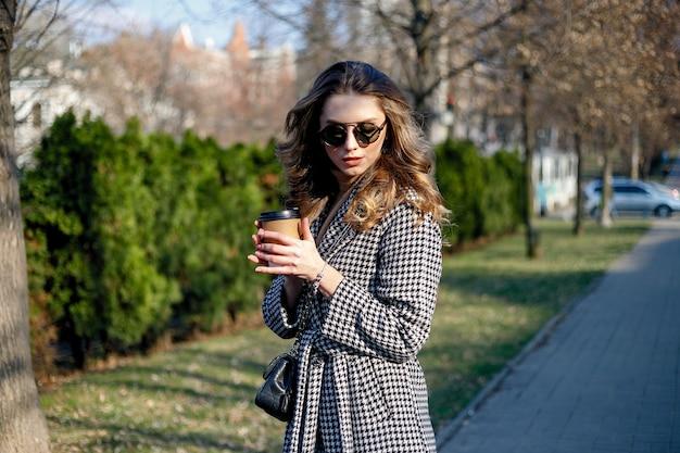 트렌치 코트를 입고 웃고 있는 우아한 여성이 종이컵으로 커피를 마시며 걷고 있습니다. 곱슬 머리를 가진 웃는 여자 카메라를보고 미소 걷기 슬로우 모션 얼굴 일몰 아름다운 여자 야외 근접 촬영 귀엽다