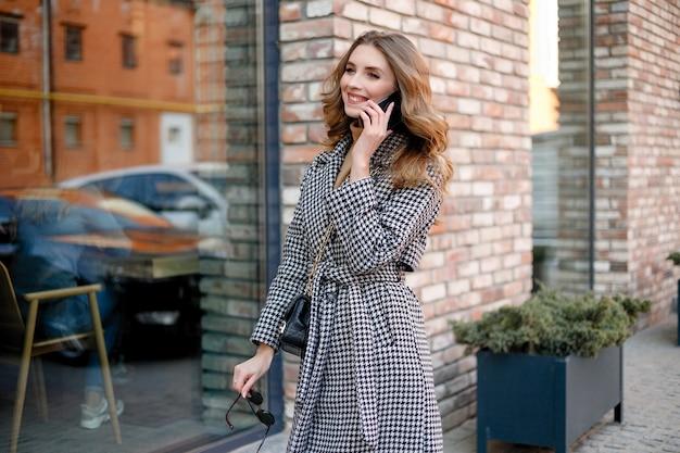 Улыбается элегантная женщина в пальто, идя и пить кофе из бумажного стаканчика. улыбается женщина с вьющимися волосами смотреть в камеру улыбка ходьба медленное движение лицо закат красивая дама на открытом воздухе крупным планом мило