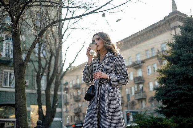 コーヒー カップを持って歩くトレンチ コートを着た笑顔のエレガントな女性
