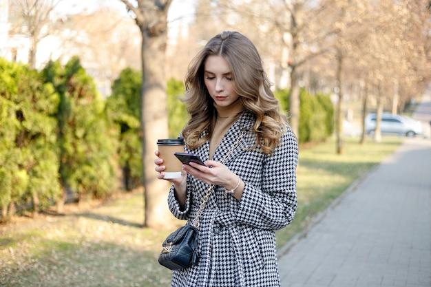 携帯電話とコーヒーを持って歩くトレンチ コートを着た笑顔のエレガントな女性