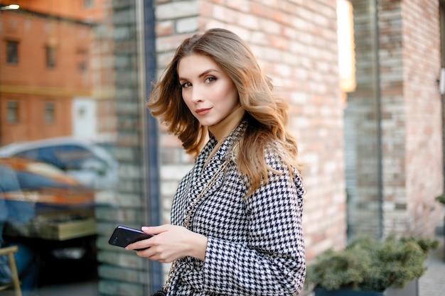 携帯電話を持って歩くトレンチ コートを着た笑顔のエレガントな女性