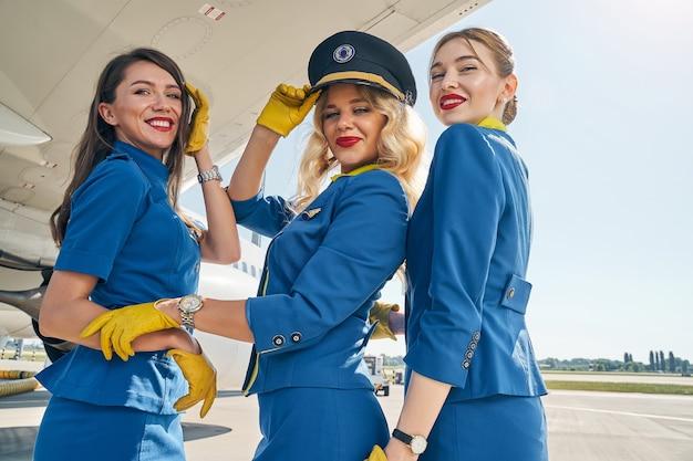 Улыбающаяся элегантная молодая стюардесса в пилотской фуражке и ее коллеги в униформе смотрят вперед