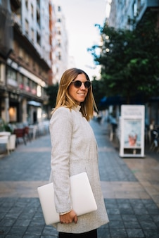 Smiling elegant young woman with sunglasses and laptop on street