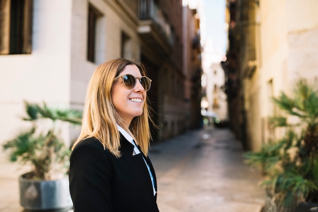 Smiling elegant young woman with sunglasses on narrow street