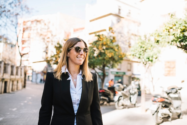 Smiling elegant young woman with sunglasses on street