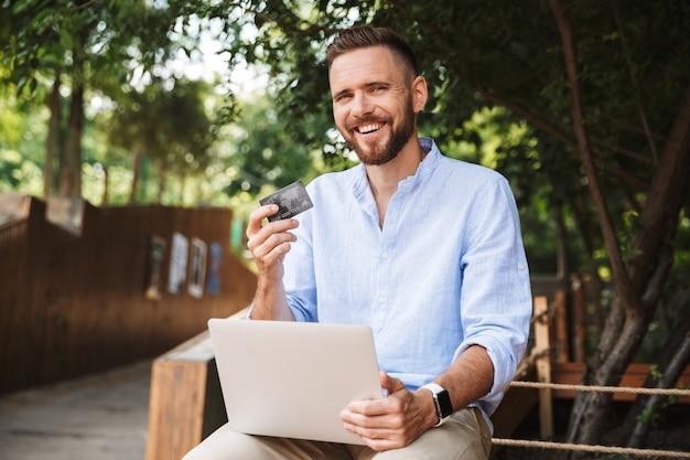 ノートパソコンを使用して感情的な若いひげを生やした男の笑顔