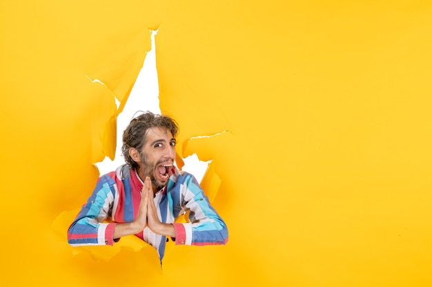 Smiling and emotional young man poses in torn yellow paper hole background making thanks gesture
