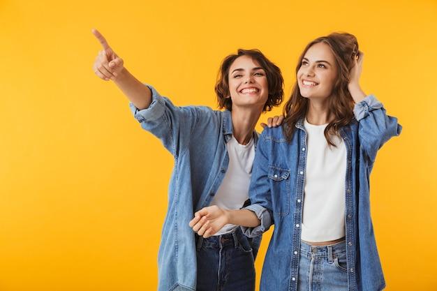 笑顔の感情的な若い女性の友人は、黄色の壁を指して孤立してポーズをとっています。