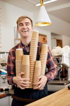 カフェで使い捨ての紙コップをたくさん飲むエプロンで笑顔の従業員バリスタ
