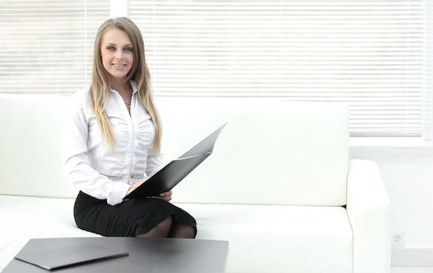 Улыбающийся сотрудник clipbord сидит в современном офисе. фотография с местом для текста