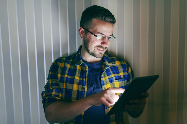 Smiling employee with eyeglasses using tablet while standing in front of wall in his office late at night