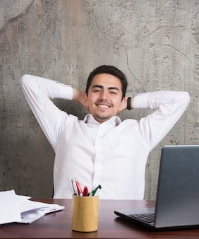 Улыбающийся сотрудник с листами бумаг и сидя за столом. фото высокого качества