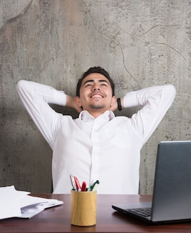 Smiling employee with sheets of papers and sitting at the desk. high quality photo