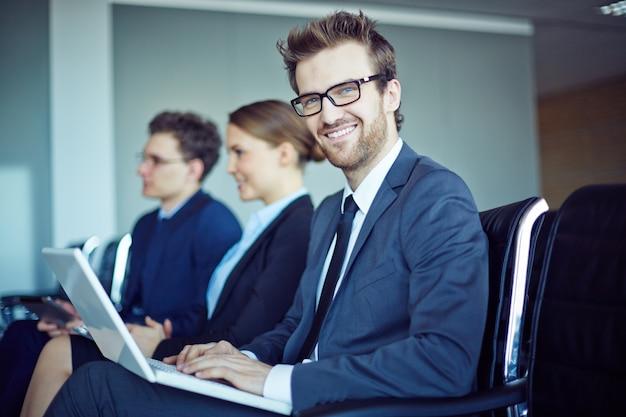 Sorridente dipendente con cravatta e laptop