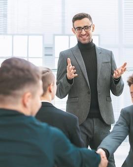 Улыбающиеся сотрудники, пожимая руки во время рабочей встречи