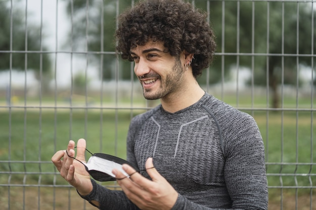 Smiling energetic spanish guy is about to put on a protective mask