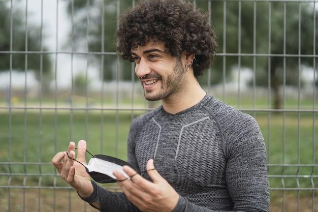 웃고 있는 활기찬 스페인 남자가 보호 마스크를 쓰려고 합니다