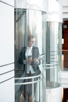 コーヒーを飲みながら、オフィスビルのエレベーターで書類を見て、元気な若いビジネスレディの笑顔
