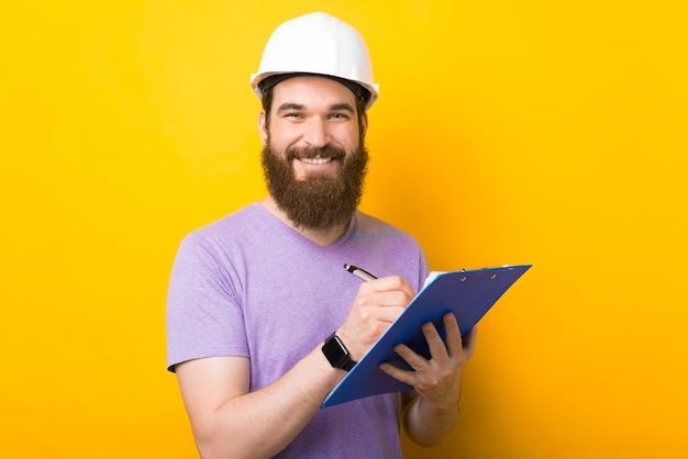 Улыбающийся инженер бородатый мужчина пишет в некоторых бумагах на желтом фоне.