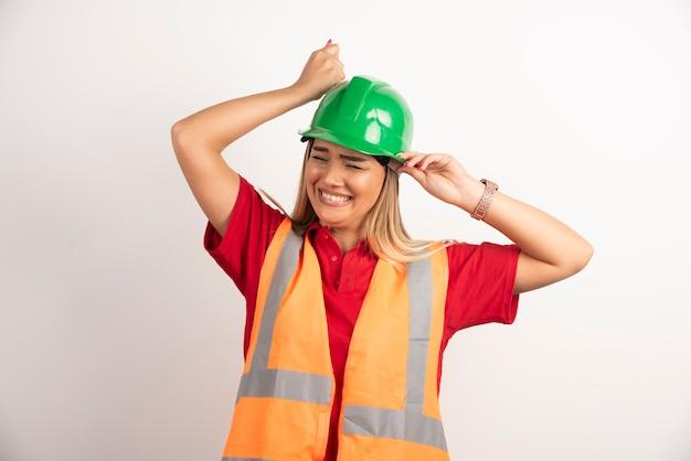 Улыбающийся инженер женской одежды носить форму с жестким зеленым шлемом на белом фоне.