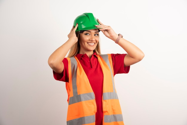 Smiling engineer female wear uniform with hard green helmet on white background.