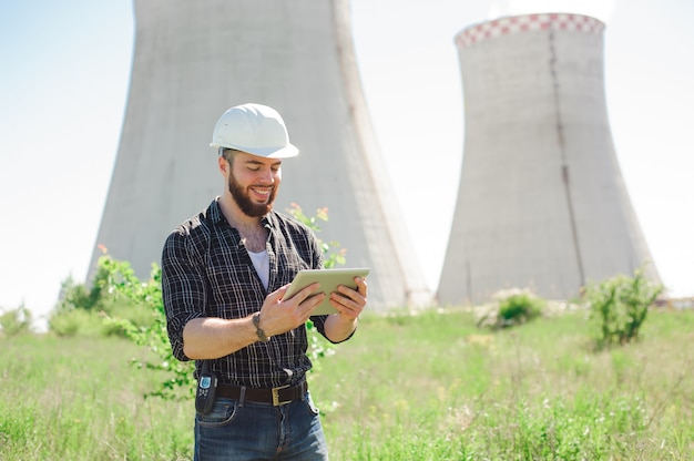 Smiling engineer using a tablet in a facility.