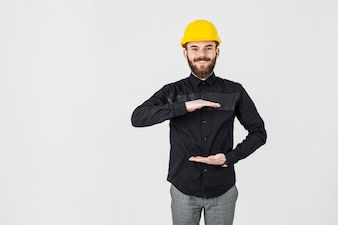 Smiling engineer wearing yellow hardhat gesturing