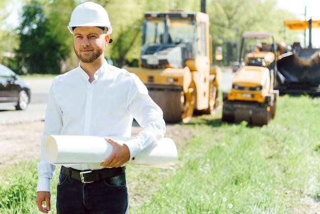Улыбающийся инженер в шлеме, стоящий перед экскаватором на строительной площадке