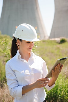 Smiling engineer woman with tablet on electric station.