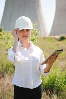 전기 역에 타블렛으로 웃는 엔지니어 여자.