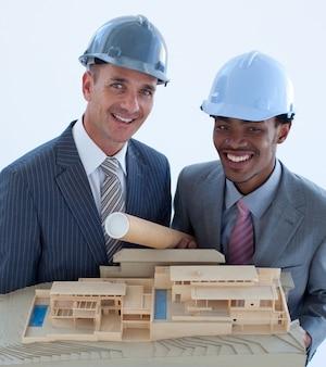 Улыбающиеся инженеры с жесткими шляпами, держащими модельный дом