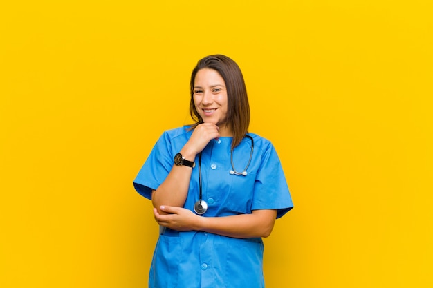Smiling, enjoying life, feeling happy, friendly, satisfied and carefree with hand on chin isolated against yellow wall