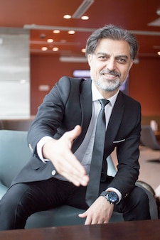 Smiling entrepreneur extending arm for handshake