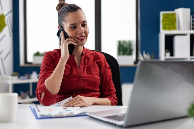 웃고 있는 기업가는 동료와 전화 통화를 하는 동안 클립보드에서 재무 차트 그래프를 확인하고 사무실 책상 작업 공간에 앉아 대화를 나누었습니다. cellp에서 클라이언트와 통신하는 관리자