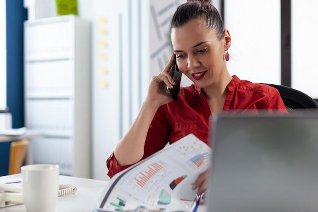 Улыбающийся предприниматель разговаривает по телефону