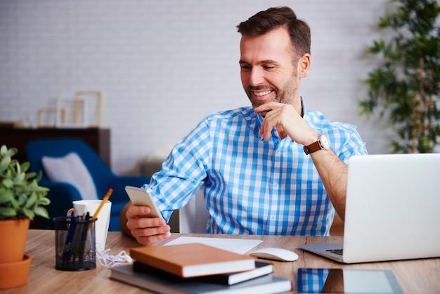 그의 사무실에서 휴대 전화를 사용하여 웃는 기업가