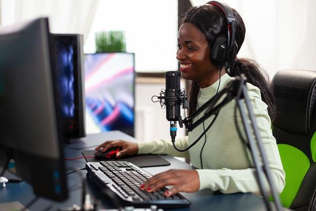 헤드폰을 끼고 웃고 있는 e스포츠 스트리머가 의자에 앉아 라이브 경쟁을 즐기고 있습니다. 온라인 챔피언십을 위해 헤드셋과 키보드를 사용하여 재미있는 비디오 게임 스트리밍.