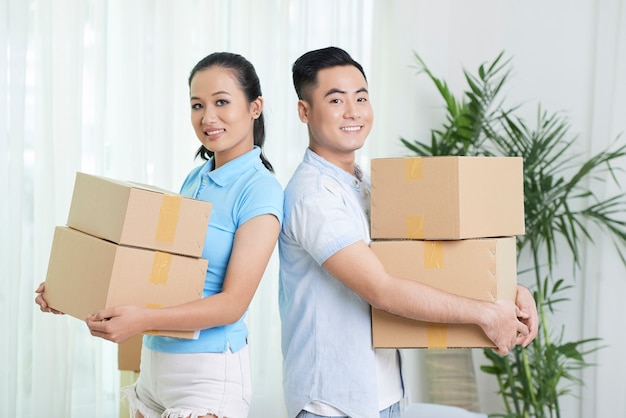 Smiling ethnic couple with carton boxes