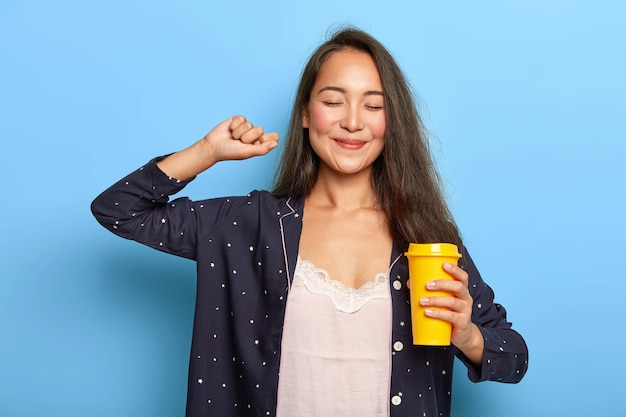 Smiling ethnic girl stretches arms after awakening, holds takeaway coffee cup, has cheerful expression, wears no makeup