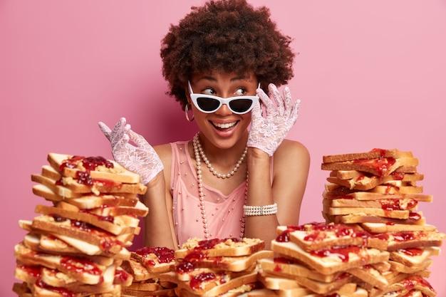 Sorridente signora etnica guarda da parte e tiene la mano sugli occhiali da sole, è di buon umore, ridacchia positivamente alla festa, indossa abiti eleganti, posa su un muro roseo, molti deliziosi panini in giro