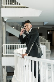 Smiling ethnic manager answering phone call on balcony