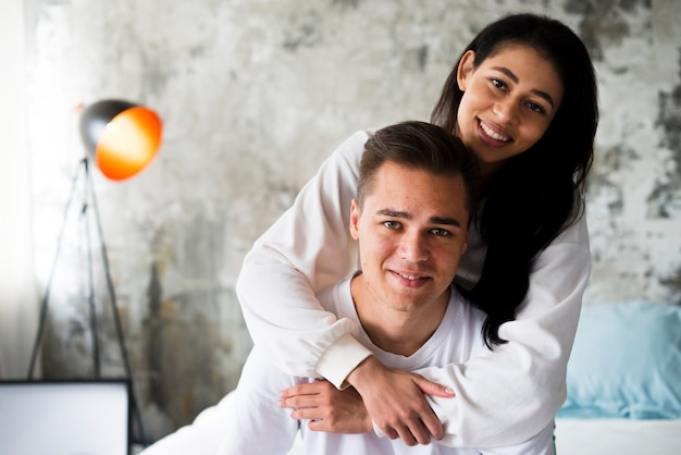 Smiling ethnic woman in white clothes hugging handsome man from behind