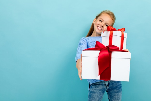 Smiling european girl holding a gift on a light blue  with copyspace