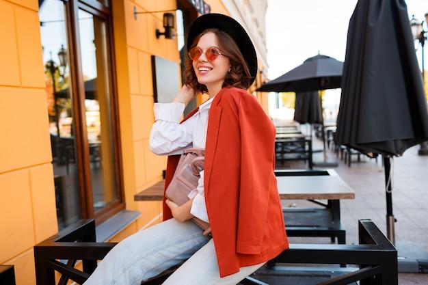 かわいいオレンジ色のサングラス、ジャケット、屋外に座っている黒い帽子で笑顔のヨーロッパの女の子。