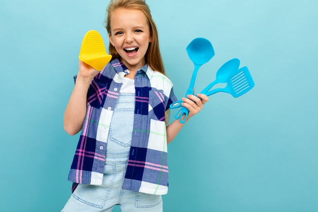 Smiling european girl with cooking utensils in hands on light blue wall